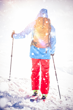 Full length rear view of skier walking on the slope with ski