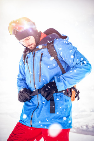 Skier tightening his backpack belt while getting ready for skiing