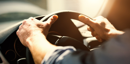 彼の車のステアリング ホイールを握って男の手をトリミング