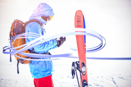 telephone poles: Grey line design against skier using mobile phone on snowy mountains