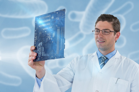 Computer engineer holding motherboard against digital image of red bacteria 3d Stock Photo