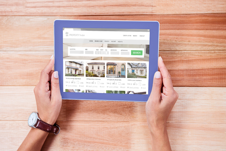 tablet pc in hand: Composite image of property web page against overhead of feminine hands using tablet