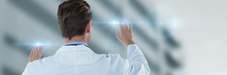 Rear view of doctor touching transparent interface against low angle view of defocused building Stock Photo