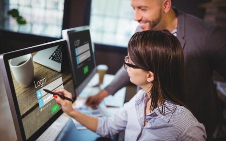 Close-up van loginpagina tegen vrouwelijke fotoredacteur die over computer met mannelijke collega bespreken Stockfoto