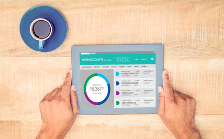 new account: Graphic image of bank account web site against hand holding on digital tablet over table by coffee Stock Photo