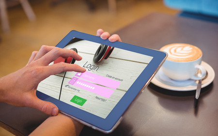 Close-up of login page against  close-up of digital tablet and coffee on table Close-up of digital tablet and coffee on table in the coffee shop