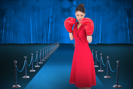 Elegant brunette in red dress wearing boxing gloves against digitally generated image of red carpet event