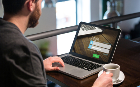 Close-up of login page against man holding coffee cup and using laptop Stock Photo