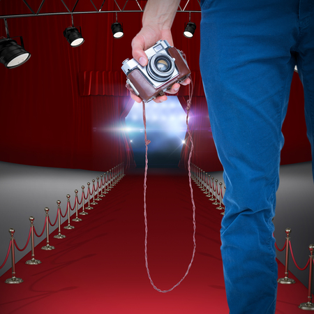 Close up view of man hand holding retro photo camera  against view of lights Stock Photo