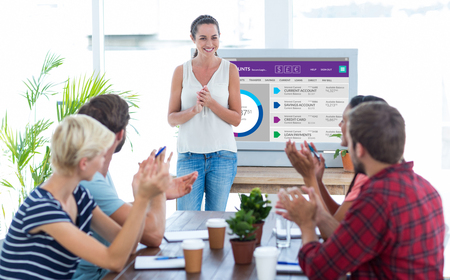 explanations: Colleagues clapping hands in a meeting against graphic image of bank account web site Stock Photo