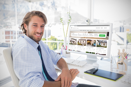 Composite image of property web site against smiling designer sitting at his desk