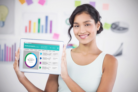 Happy businesswoman showing digital tablet in creative office against graphic image of bank account web site