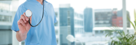 Midsection of surgeon holding stethoscope against laptop on desk by glass window in office