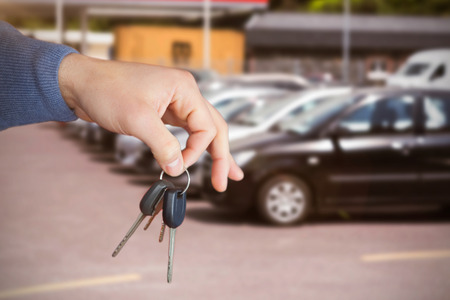 somebody: Smiling woman receiving keys from somebody against cars parked at road Stock Photo