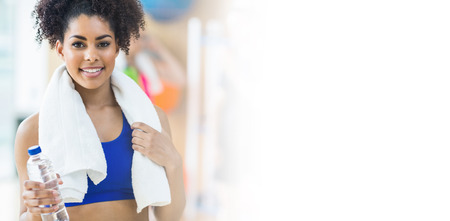 Portrait of fit woman with towel and bottle at gym