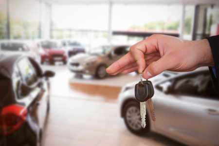 customer records: Happy woman receiving car keys against cars parked at showroom