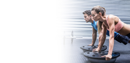 Side view of a muscular couple doing bosu ball exercises Stock Photo