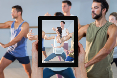 Close-up of hands holding digital tablet against group of people exercising Stock Photo