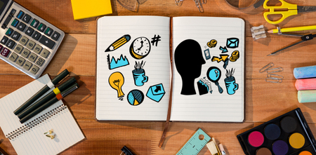 Composite image of human representation amidst different business symbols against open diary with various stationery Stock Photo