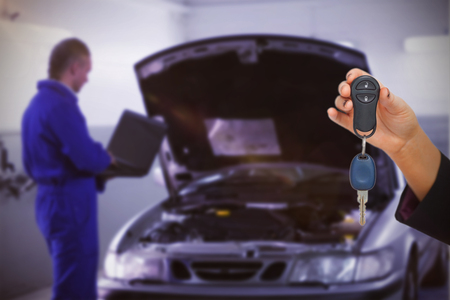 Woman holding key and small car against mechanic typing on a computer next to a car