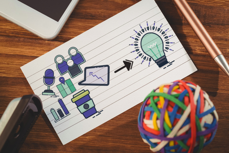 Composite image of computer icons pointing towards light bulb against paper by smartphone and colorful rubber band ball Stock Photo