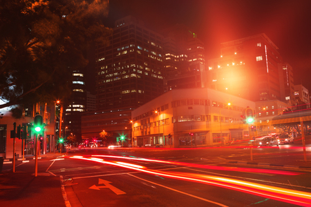 illuminated roads by building in city at night Stock Photo