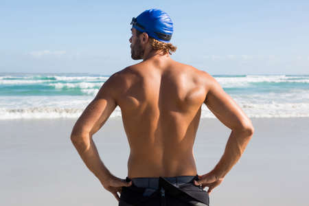 Rear view of shirtless athlete standing at beach against sky