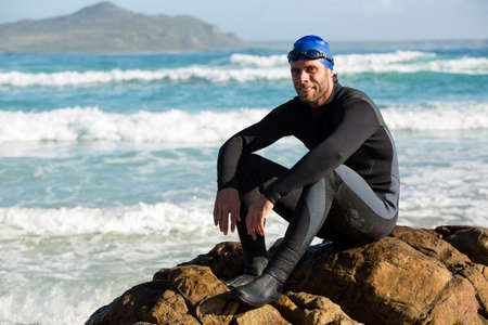 Portrait of confident athlete sitting on rock at sea shore