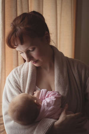 red bathrobe: Loving mother breastfeeding baby at home LANG_EVOIMAGES