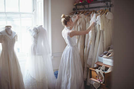 feminity: Young bride selecting wedding dress from clothes hanger in a boutique