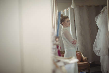 feminity: Young bride looking at herself in mirror at boutique