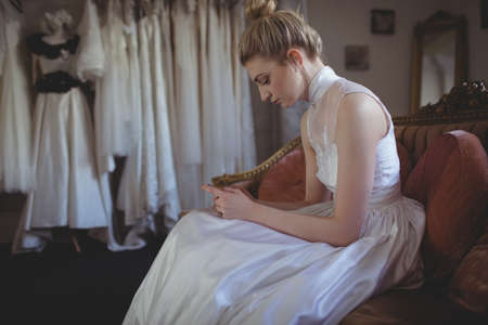 feminity: Young bride using mobile phone in a boutique LANG_EVOIMAGES