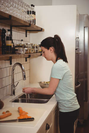 cleaning service: Side view of female chef washing carrot under the tap in professional kitche LANG_EVOIMAGES