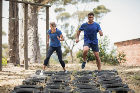 Man and woman running over the tyre during obstacle course in boot camp