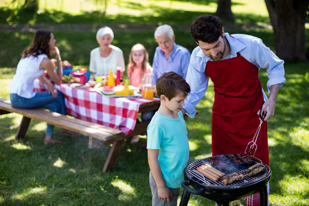 Father and son barbequing in the park during day Stock Photo