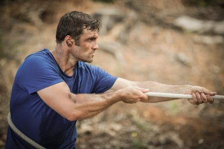 Hombre jugando tira y afloja durante la carrera de obstáculos en el campo de entrenamiento