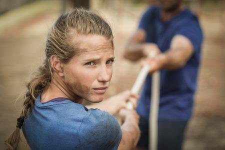 Uomo e donna che giocano conflitto durante la corsa ad ostacoli nel campo di addestramento Archivio Fotografico - 75346210