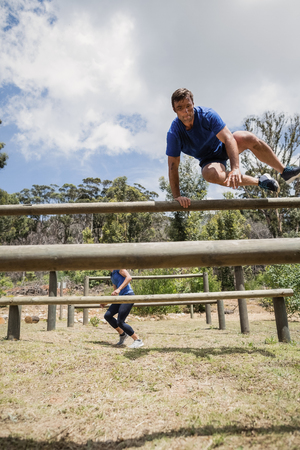 Man and woman jumping over the hurdles during obstacle course in boot camp Stock Photo