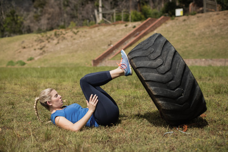 military press: Fit woman performing leg workout with tier during obstacle course in boot camp Stock Photo