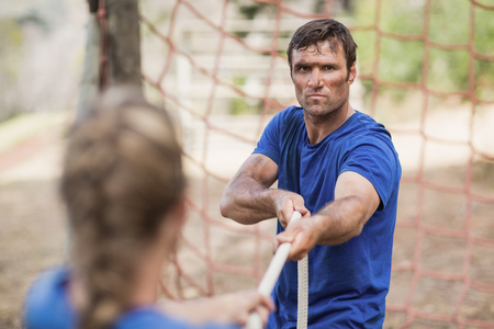 Man and woman playing tug of war during obstacle course in boot camp