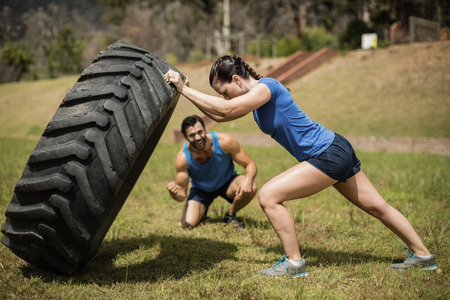 Fit woman flipping a tire while trainer cheering during obstacle course in boot camp