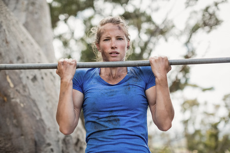 Fit woman performing pull-ups on bar during obstacle course in boot camp