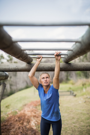 Fit woman climbing monkey bars during obstacle course in boot camp Stock Photo
