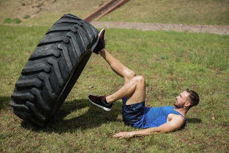 military press: Fit man performing leg workout with tier during obstacle course in boot camp