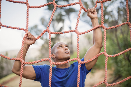 Fit man climbing a net during obstacle course in boot camp