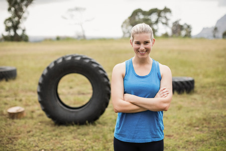 Fit woman standing with arms crossed in boot camp on a sunny day