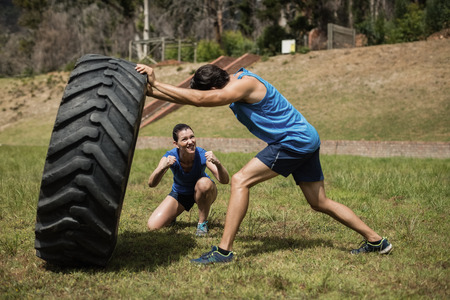 Fit man flipping a tire while trainer cheering during obstacle course in boot camp Stock Photo