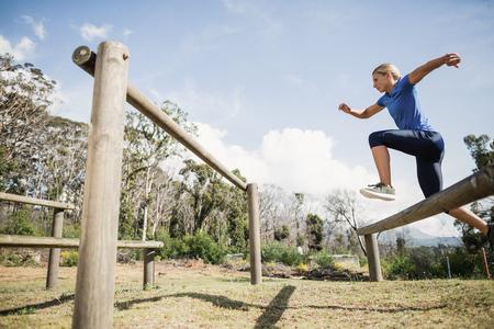 Femme sautant par-dessus les obstacles pendant le parcours du combattant dans le camp d'entraînement Banque d'images - 75346327