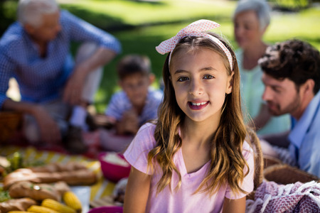 Portrait of girl with hairband and family enjoying the picnic in background Stock Photo