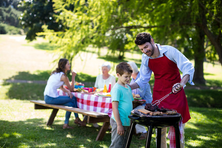 Father and son barbequing in the park during day 写真素材